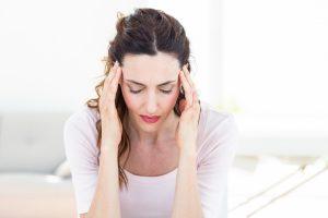 Junge Frau massiert sich die Schläfe um die Kopfschmerzen zu lindern.