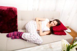 Junge Frau liegt mit Bauchschmerzen auf der Couch.