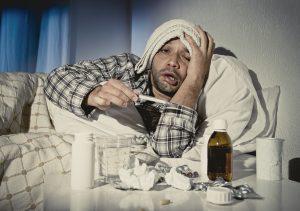 Mann liegt mit starker Erkältung im Bett.