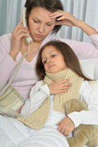 Mutter und kranke Tochter im Bett. Mutter ruft einen Arzt an.