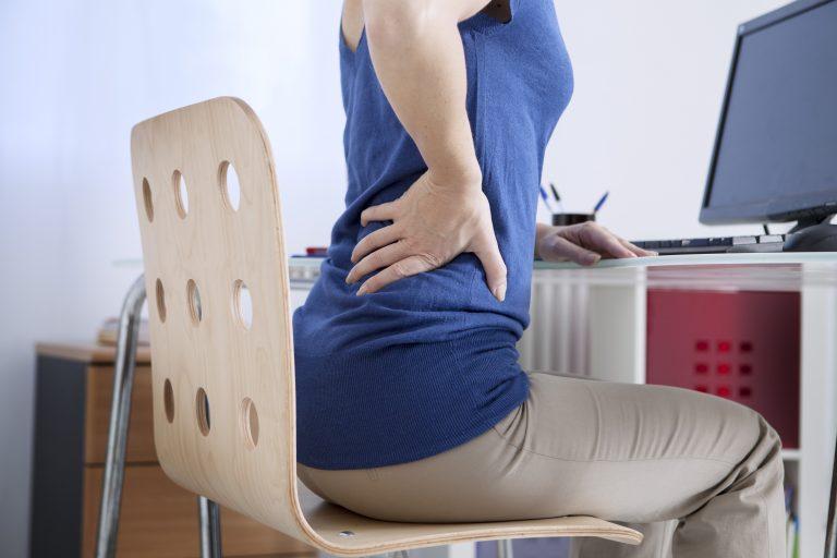 Frau sitzt mit Rückenschmerzen am Schreibtisch.